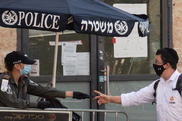 Archivo - Una policía de Israel habla con un hombre en Jerusalén durante la pandemia de coronavirus