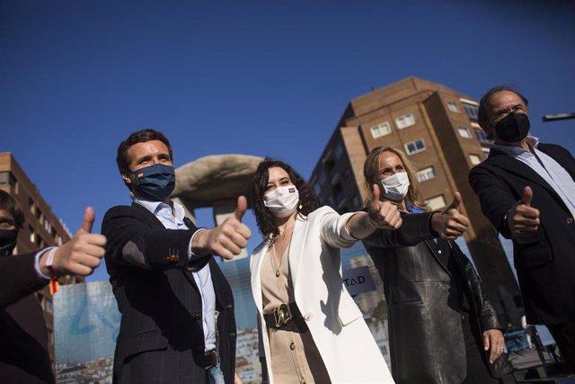 El presidente del PP, Pablo Casado; la presidenta de la Comunidad de Madrid, Isabel Díaz Ayuso, en el acto de pegada de carteles del partido de cara a las elecciones madrileñas, a 17 de abril de 2021, en Madrid (España).