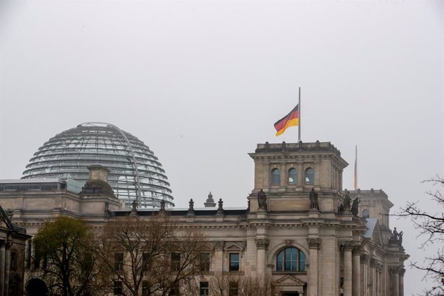 18 April 2021, Berlin: The German flag on top of the Reichstag building flies at half-mast during a commemorative event for all those who have died since the outbreak of the coronavirus (COVID-19). Photo: Christoph Soeder/dpa