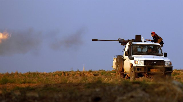 Archivo - 02 November 2019, Syria, Tall Tamr: A fighter of the People's Protection Units (YPG) Kurdish group fires his truck-mounted machine gun during clashes with Turkish forces. Photo: Carol Guzy/ZUMA Wire/dpa