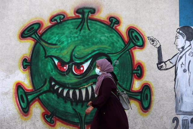 06 April 2021, Palestinian Territories, Gaza: A Palestinian woman walks past by a coronavirus mural. Photo: Ashraf Amra/APA Images via ZUMA Wire/dpa