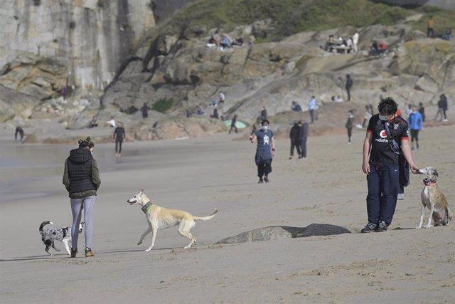 Archivo - Varias personas disfrutan de un día de primavera en la playa del Orzán, en A Coruña