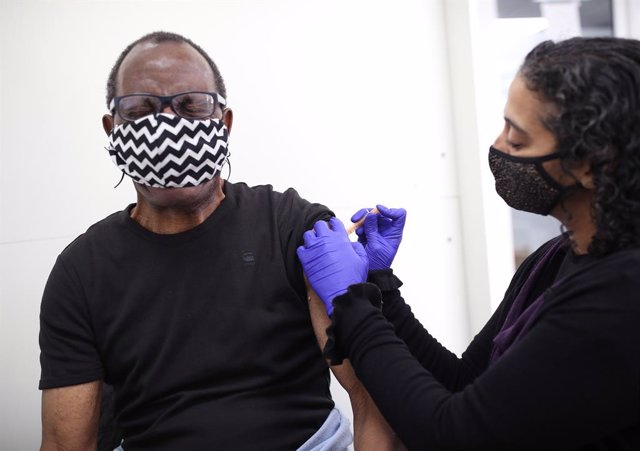 09 April 2021, United Kingdom, London: Pharmacist Asha Fowells (R) vaccinates Paul Jinadu,79, with his second dose of the Oxford/AstraZeneca coronavirus vaccine, at Copes Pharmacy and Travel Clinic in Streatham, south London. Photo: Yui Mok/PA Wire/dpa