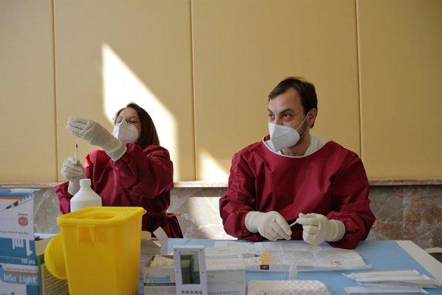 Dos trabajadores sanitarios en un centro de vacunación en Napoles.