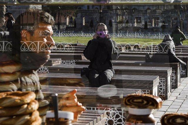 Archivo - Una mujer con mascarilla en una plaza de Estambul, en Turquía