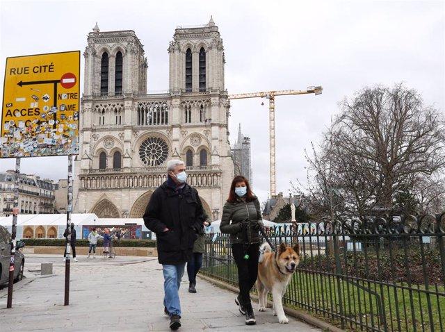 Archivo - Un pareja con mascarilla camina por las inmediaciones de la catedral de Notre Damme de París