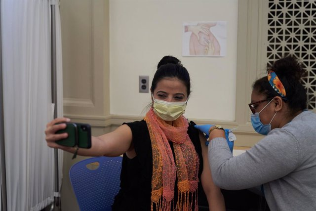 Archivo - 21 December 2020, US, Worcester: A woman takes a selfie as she receives her Pfizer Coronavirus (Covid-19) vaccine at a vaccination centre in UMass Memorial Hospital in Worcester. Photo: Allison Dinner/ZUMA Wire/dpa