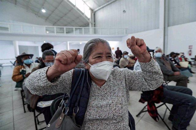 Una mujer celebra haber recibido el imunizador contra la COVID-19 en México