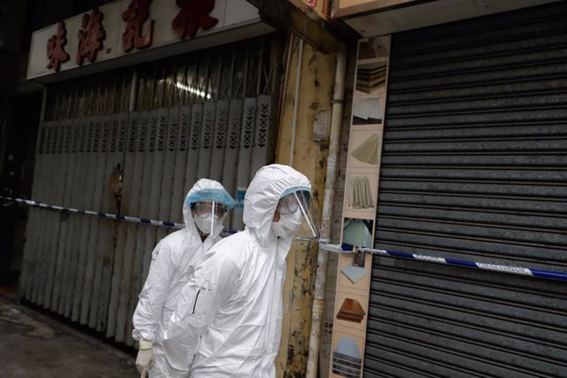 Archivo - 23 January 2021, China, Hong Kong: Sanitizing team stand in front of closed shops in Yau Tsim Mong district where unprecedented lockdown has been declared early this morning by Hong Kong government in order to carry out compulsory coronavirus (C