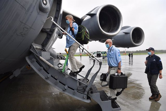 AUSMAT medical team members Angela Jackson (left), Dr Mark Little (centre) and Leigh Cox (right) are seen boarding a C-17A Globemaster at RAAF Base Amberley, west of Brisbane, Tuesday, March 23, 2021. Australia are sending 8,000 doses of its COVID-19 vacc