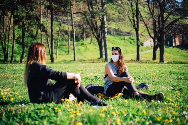 Archivo - Dos mujeres charlan sentadas en el cesped. Primavera. Amigas.