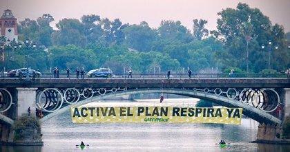 Greenpeace descuelga una pancarta en el puente de Triana para pedir la activación urgente del Plan Respira