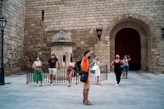 Varios turistas junto al Palacio de la Almudaina de Palma de Mallorca durante el primer día de uso obligatorio de la mascarilla en Baleares por el Covid-19, en Palma de Mallorca, Islas Baleares (España) a 13 de julio de 2020