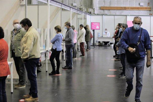 Varias personas esperan para ser vacunadas en el primer día de la vacunación masiva en la Comunidad Valenciana, a 19 de abril de 2021, en la Ciudad de la Luz, Alicante, Comunidad Valenciana, (España).
