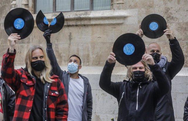 Varios Dj de la Comunidad Valenciana sostienen discos como signo de protesta durante una concentración organizada frente al Palau de la Generalitat
