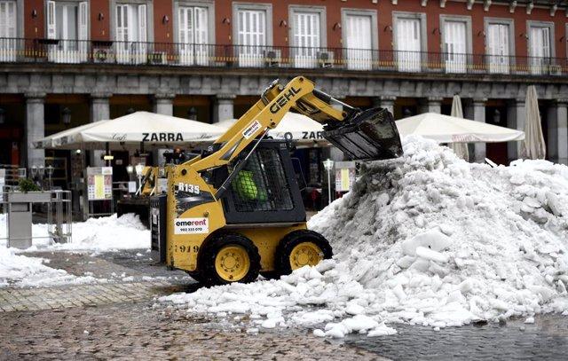 Archivo - Una máquina excavadora continúa con las tareas de limpieza de calles tras la gran nevada provocada por la borrasca 'Filomena', en la Plaza Mayor, Madrid (España), a 20 de enero de 2021