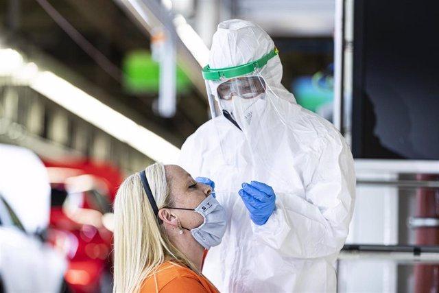 Un sanitario realiza un test de antígenos a una trabajadora de Seat al lado de la línea de producción.