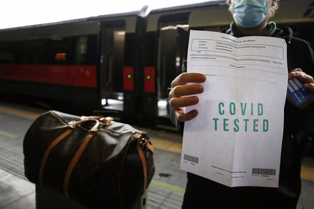 16 April 2021, Italy, Rome: A passenger shows the result of the coronavirus (COVID-19) swab test at Roma Termini Railway station before boarding the newly inaugurated Rome-Milan Trenitalia train, only passengers with negative results of the COVID-19 swab