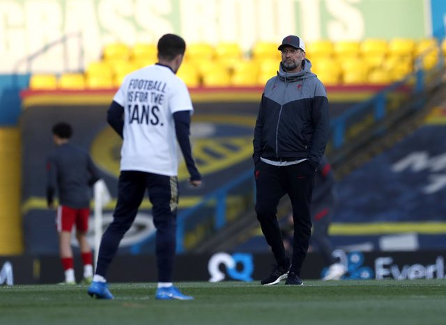 19 April 2021, United Kingdom, Leeds: Liverpool manager Jurgen Klopp looks on as a Leeds United player warms up wearing a shirt opposing the new European Super League ahead of the English Premier League soccer match between Leeds United and Liverpool at E