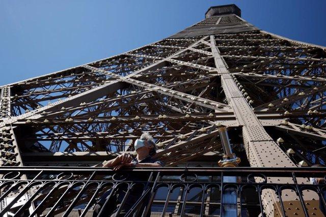 Archivo - Un hombre con una mascarilla en la Torre Eiffel de París