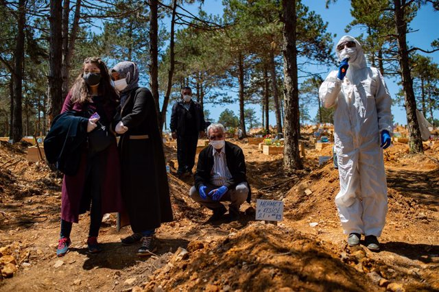 Archivo - 30 May 2020, Turkey, Istanbul: People mourn and pray in a cemetery over the grave of a relative who died of Coronavirus (COVID-19), next to a morgue worker wearing a protective suit. Photo: Yasin Akgul/dpa