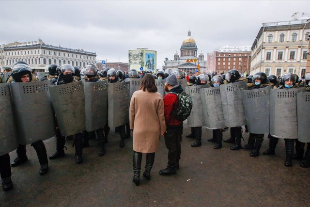 Archivo - 31 January 2021, Russia, Saint Petersburg: A couple stands in front of Russian National guard officers who are blocking a street during a demonstration against the detention of the Russian opposition leader Alexey Navalny. Navalny was immediatel