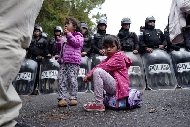 Archivo - 16 January 2019, Guatemala, Aguas Calientes: A migrant child sits on his backpack in front of a number of police officers at the Aguas Calientes border crossing between Honduras and Guatemala, as she takes her way to the north, plans to immigrat