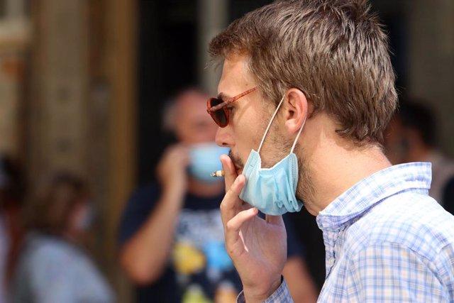 Archivo - Una persona fuma en la calle durante el primer día de la prohibición de realizarlo en la vía pública en Andalucía si no existe una distancia de dos metros de separación con otras personas para evitar contagios de Covid-19.
