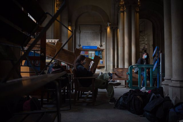 Una estudiant llegeix a la barricada del Sepc per bloquejar l'accés a l'edifici històric de la UB.