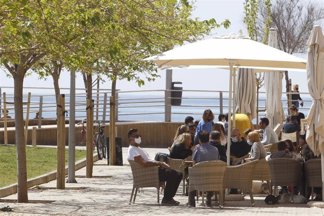 Varias personas en la terraza de un bar.