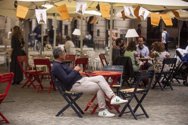 Una persona en un bar decorado con los farolillos tradicionales de la Feria de Abril, suspendida por segundo año consecutivo debido a la pandemia provocada por el coronavirus, Covid-19. En Sevilla (Andalucía, España), a 20 de abril de 2021.