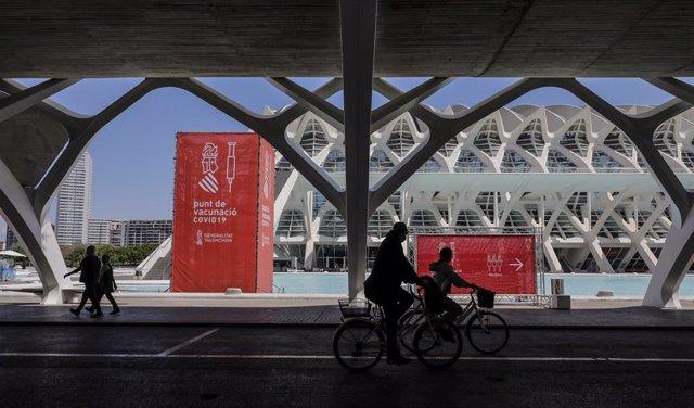 Diverses persones passen pel punt de vacunació de la Ciutat de les Arts i les Ciències de València