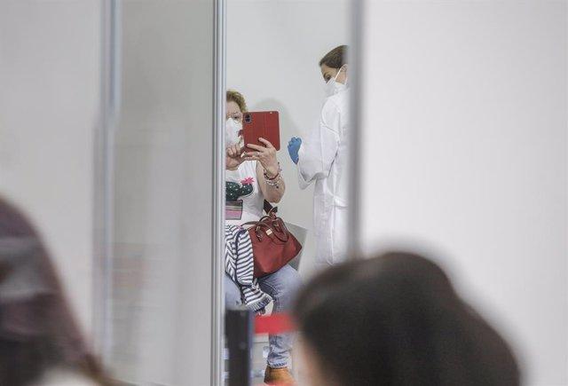 Una dona es pren un selfie mentre és vacunada en el primer dia de la vacunació massiva a la Comunitat Valenciana