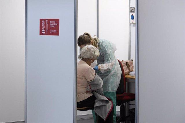 Una sanitaria vacuna a una mujer en el primer día de la vacunación masiva en la Comunidad Valenciana, a 19 de abril de 2021, en el Auditori de Castellón, Comunidad Valenciana, (España).