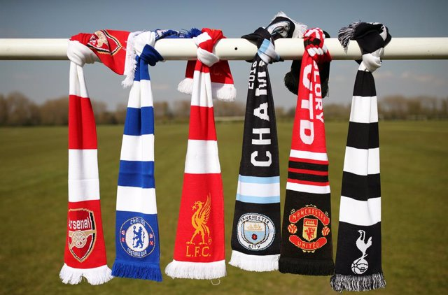 19 April 2021, United Kingdom, London: A selection of scarves bearing the crests of English soccer Premier League teams (L-R) Arsenal, Chelsea, Liverpool, Manchester City, Manchester United and Tottenham Hotspur are seen at Hackney Marshes after the clubs