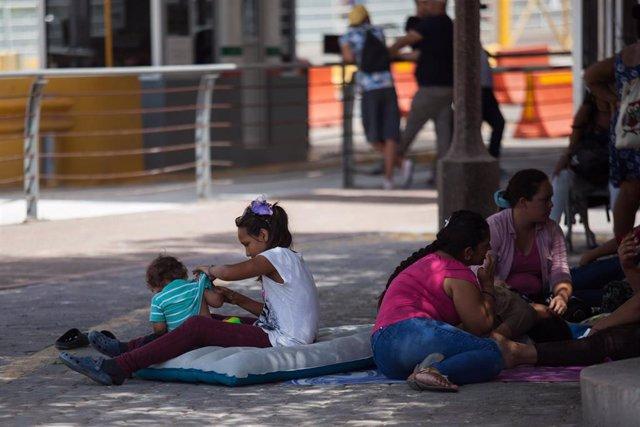 Archivo - Niños esperan para solicitar asilo en Estados Unidos