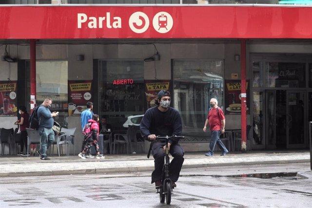 Archivo - Transeúntes pasean cerca de la estación de Cercanías de Parla, Madrid (España).