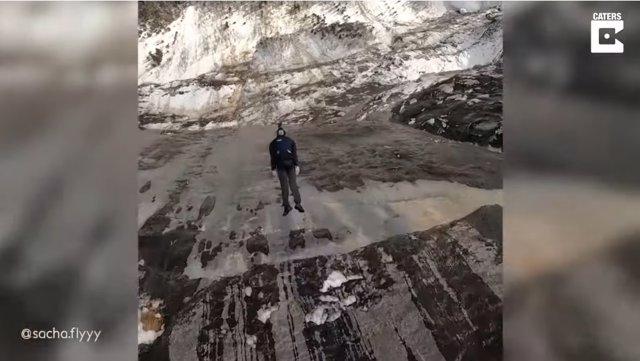 Un hombre graba el impresionante salto que realiza su compañero mientras practican salto BASE