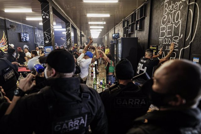 21 April 2021, Brazil, Jandira: Bar-goers stand with their heads above their heads during a police raid to break up a social gathering amid the coronavirus pandemic. Photo: Marcelo Chello/ZUMA Wire/dpa