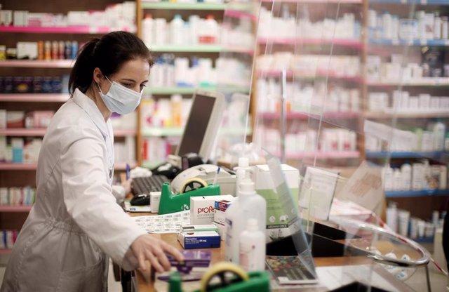 Archivo - Una farmacéutica con mascarilla despacha en una farmacia el día en que el Boletín Oficial del Estado (BOE) publica el acuerdo de la Comisión Interministerial de Precios de los Medicamentos que fija el importe maximo de las mascarillas quirúrgica