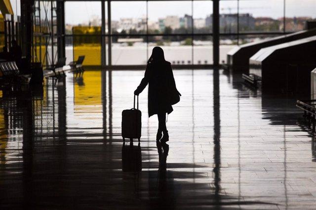 Una mujer con una maleta en el aeropuerto de Madrid - Barajas Adolfo Suárez, a 21 de abril de 2021, en Madrid (España). La titular del Juzgado de Instrucción número 15 de Madrid ha incoado diligencias previas contra el expresidente en funciones de la Soci