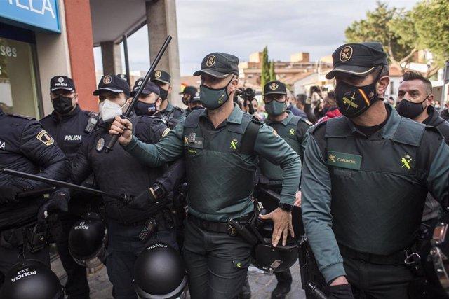 Un grupo de agentes vigila y se protege durante un mitin de Vox, a 21 de abril de 2021, en Navalcarnero, Madrid (España).