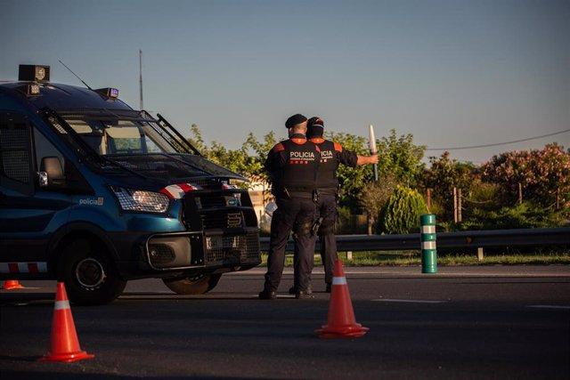 Archivo - Dos Mossos d'Esquadra controlan un acceso de carretera por las restricciones de movilidad decretadas a causa de la pandemia de coronavirus (Archivo)