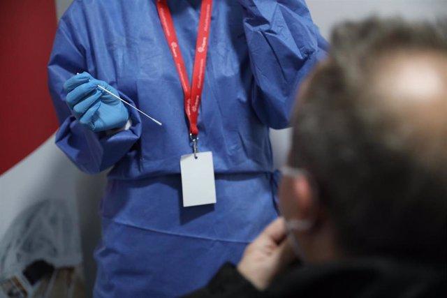 Archivo - Un sanitario se dispone a realizar un test de antígenos