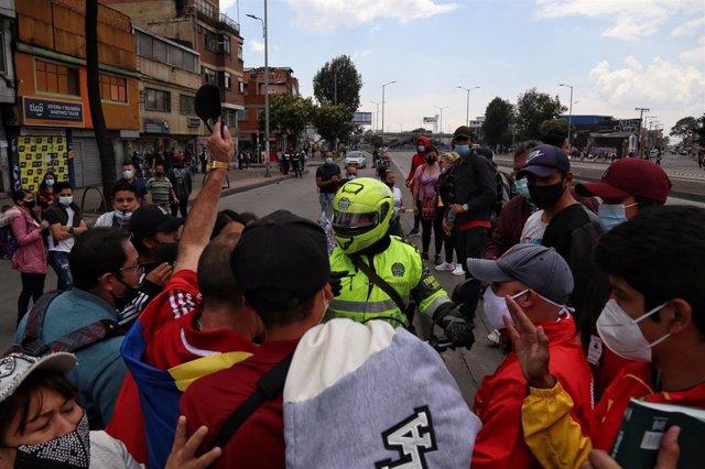 Un grupo de manifestantes se enfrenta con un motociclista durante una manifestación contra las restricciones impuestas para frenar la propagación de la pandemia de coronavirus en Bogotá.