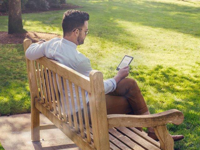 Archivo - Hombre leyendo en el parque en un Kindle