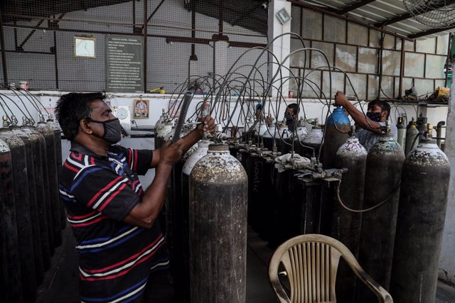 21 April 2021, India, New Delhi: Workers refill medical oxygen cylinders at a charging station during the second wave of the Covid-19 pandemic. Photo: Naveen Sharma/SOPA Images via ZUMA Wire/dpa