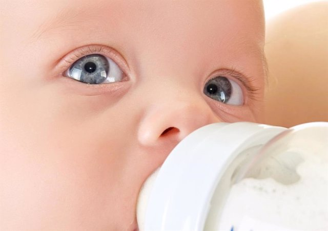 Archivo - Bebé bebiendo leche en un biberón.