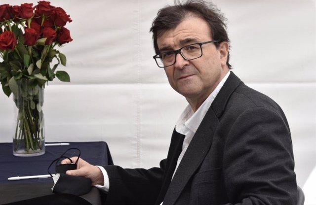 El escritor Javier Cercas firma libros en la Diada de Sant Jordi de 2021, en un recinto perimetrado por la pandemia del Covid-19.