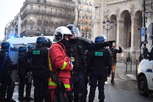 Archivo - Un bombero junto a agentes de la Policía en París durante las manifestaciones contra la reforma de las pensiones.